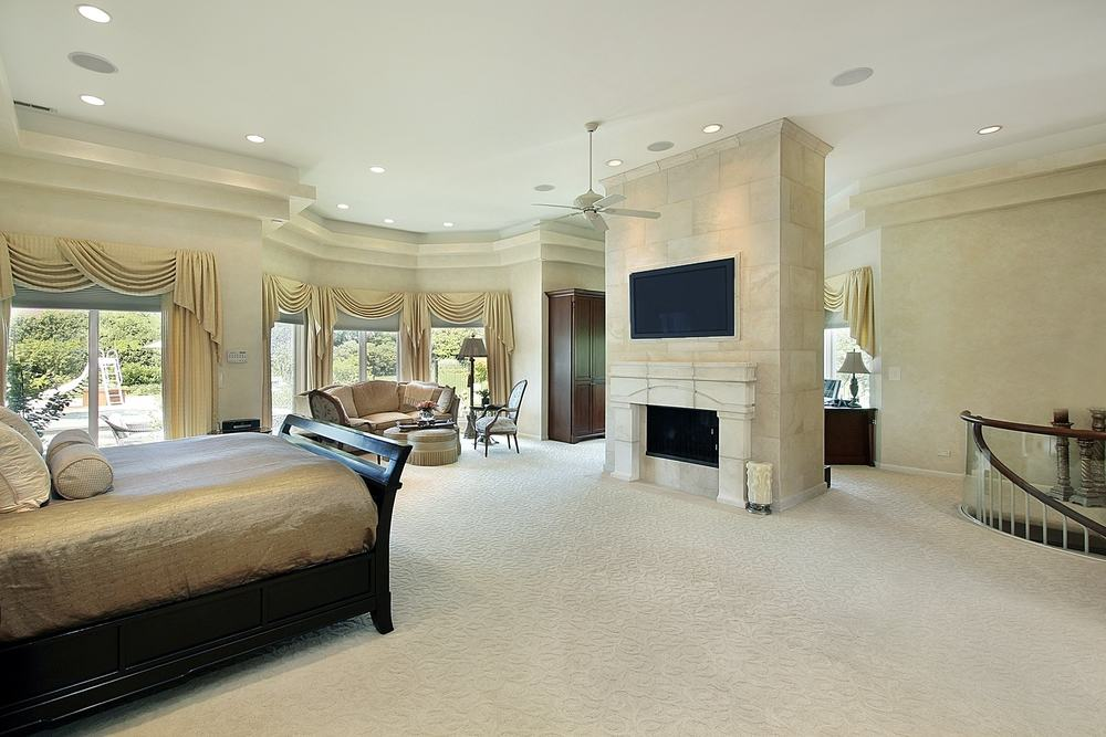 Bedroom with spiral stairs facing tv fireplace