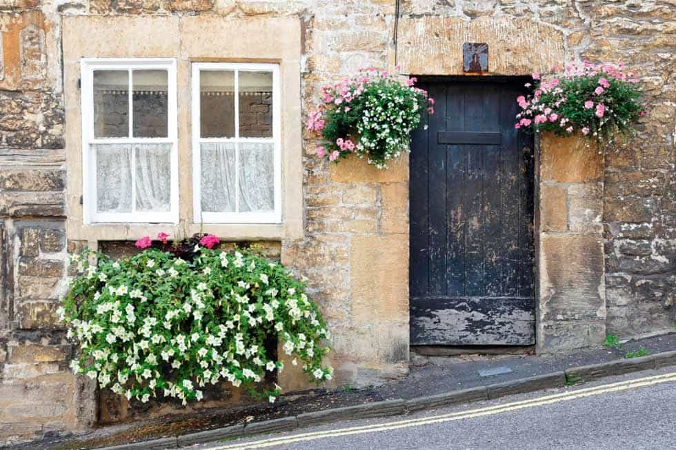 This poorly maintained front door is balanced with beautiful flowers.